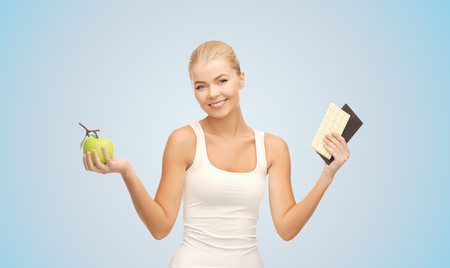 healthy eating, slimming and diet concept - happy woman choosing between green apple and chocolate over blue background