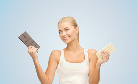 healthy eating, slimming and diet concept - happy woman choosing between dark and white chocolate over blue background