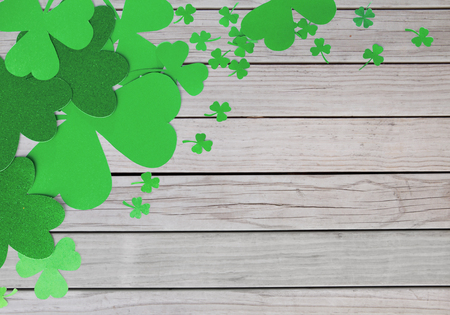 fortune, luck and st patricks day concept - green paper shamrocks on wooden grey boards background Stock Photo