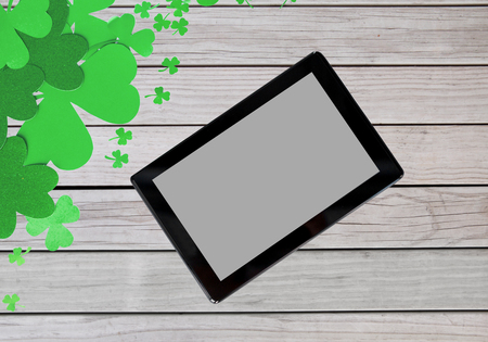 holidays and technology concept - tablet pc computer and st patricks day decorations made of paper on wooden grey boards background Stock Photo