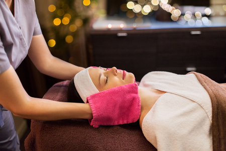 people, beauty, lifestyle and relaxation concept - beautiful young woman lying with closed eyes and having face massage with terry gloves at spa parlor