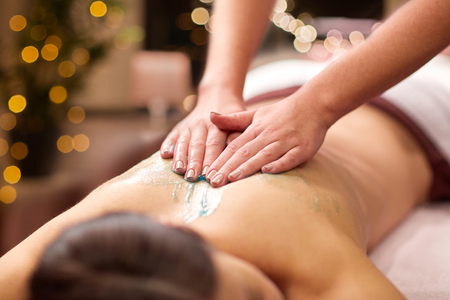 people, beauty, healthy lifestyle and relaxation concept - beautiful young woman lying and having back massage with gel at spa