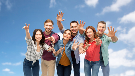 friendship and people concept - group of happy students over blue sky and clouds background