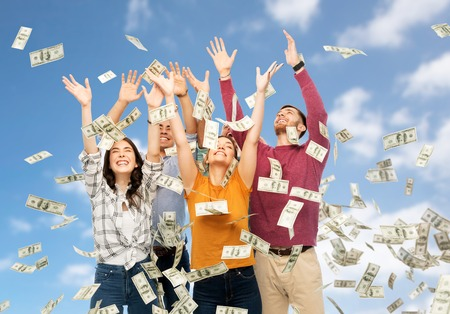 finance, wealth and people concept - group of happy friends picking money falling from up above over blue sky and clouds background