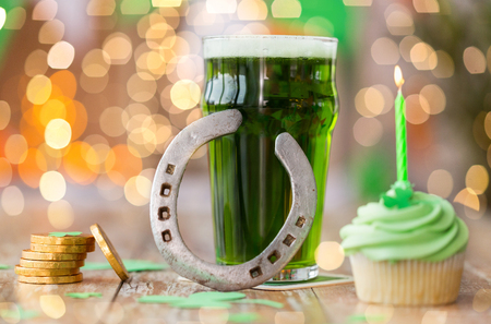 st patricks day, holidays and celebration concept - glass of green beer, cupcake with candle, horseshoe and gold coins on wooden table Stock Photo