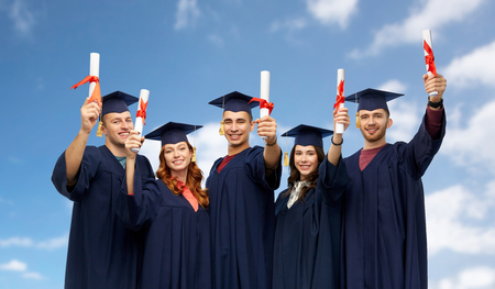 education, graduation and people concept - group of happy graduate students in mortar boards and bachelor gowns with diplomas over blue sky and clouds background Stock Photo