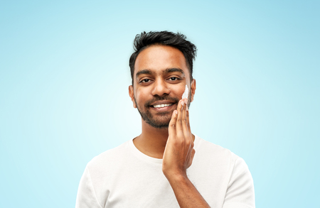 grooming, skin care and people concept - smiling young indian man applying cream to face over blue background