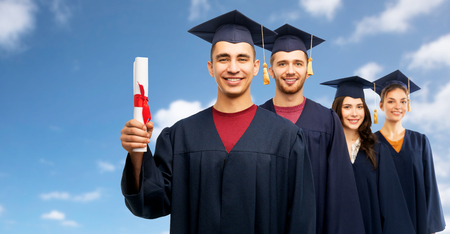 education, graduation and people concept - group of happy graduate students in mortar boards and bachelor gowns with diploma over blue sky and clouds background