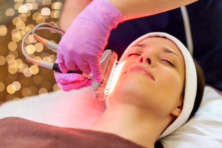 people, beauty, cosmetic treatment, cosmetology and technology concept - beautician with microdermabrasion device doing face exfoliation to young woman lying at spa Stock Photo