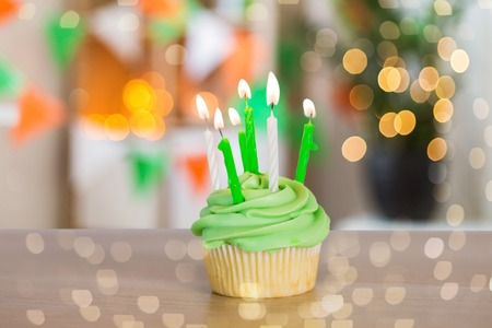 st patricks day, birthday, holidays and celebration concept - green cupcake with six burning candles on table over background of room decorated for party Stock Photo