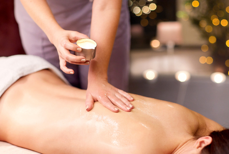 people, beauty, healthy lifestyle and relaxation concept - beautiful young woman lying and having back massage with hot oil at spa