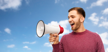 communication and people concept - smiling young man with megaphone over blue sky and clouds background