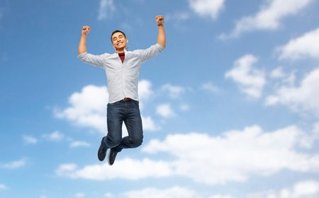 triumph, power and people concept - happy young man jumping over blue sky and clouds background