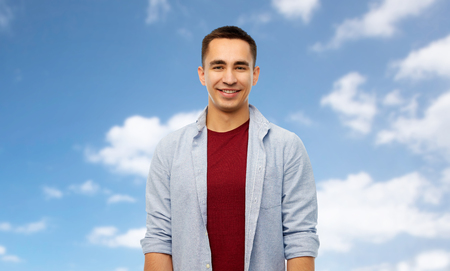 people concept - smiling young man over blue sky and clouds background