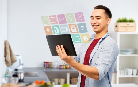 smart home, technology and people concept - happy young man tablet computer over kitchen background