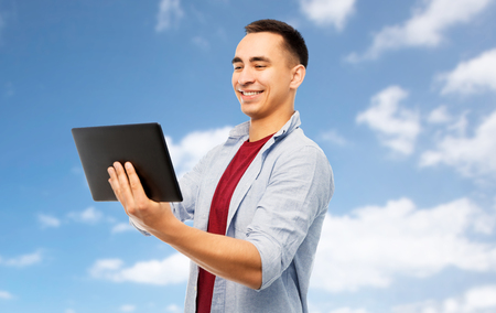 technology and people concept - happy young man tablet computer over blue sky and clouds background