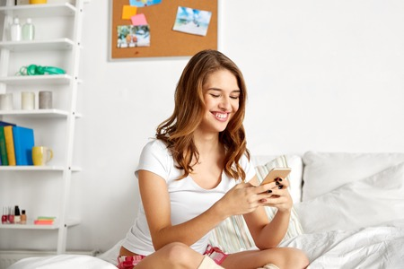 friendship, pajama party and technology concept - happy teenage girl with smartphone at home