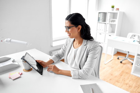 business, technology and people concept - indian businesswoman with tablet pc computer working at office