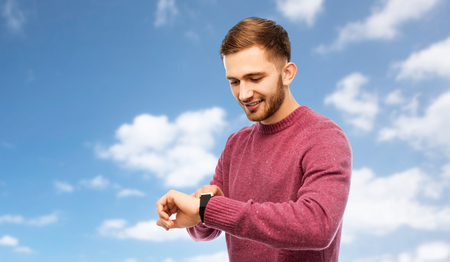 time, punctuality and people concept - smiling young man looking at wristwatch over blue sky and clouds background Stock Photo