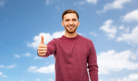 gesture and people concept - happy young man showing thumbs up over blue sky and clouds background Banco de Imagens