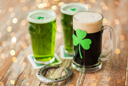 st patricks day, holidays and celebration concept - shamrock on glasses of beer and horseshoe on wooden table
