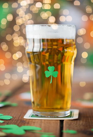 st patricks day, holidays and celebration concept - close up of glass of light beer with shamrock decoration on wooden table Stock Photo