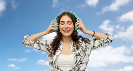 music, technology and people concept - happy young woman or teenage girl with headphones over blue sky and clouds background