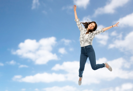 motion, freedom and people concept - happy young woman or teenage girl jumping over blue sky and clouds background