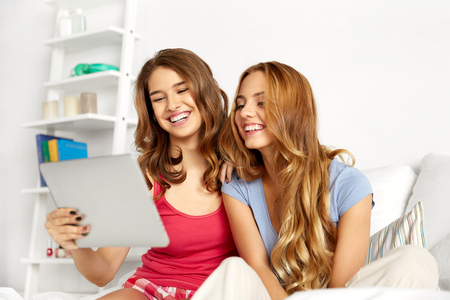 friendship, pajama party and technology concept - happy friends or teenage girls with tablet pc computer at home Stock Photo