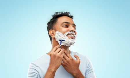 grooming and people concept - young indian man shaving beard with manual razor blade over blue background