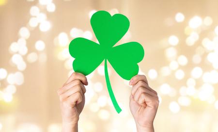 fortune, luck and st patricks day concept - hands holding green paper shamrock over festive lights on beige background