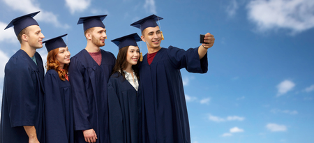 education, graduation and people concept - group of happy graduate students in mortar boards and bachelor gowns taking selfie by smartphone over blue sky and clouds background