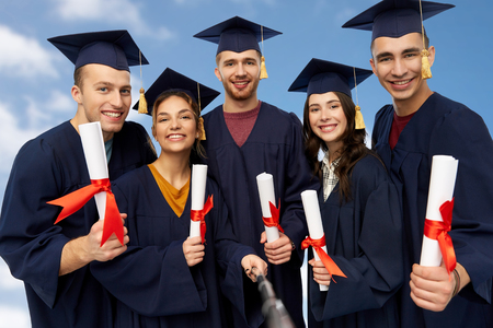 education, graduation and people concept - group of happy graduate students in mortar boards and bachelor gowns with diplomas taking picture by slfie stick over blue sky and clouds background