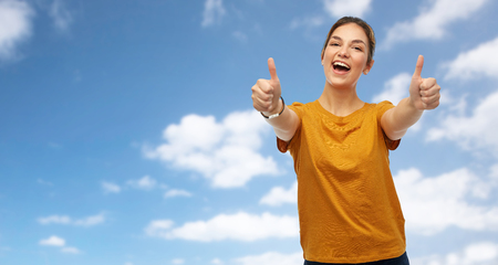 gesture and people concept - happy smiling young woman or teenage girl in orange t-shirt showing thumbs up over blue sky and clouds background