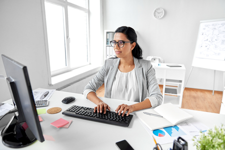 business, people and technology concept - businesswoman with computer working at office