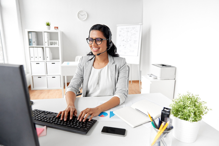 communication, business, people and technology concept - indian businesswoman or helpline operator with headset and computer talking and typing at office