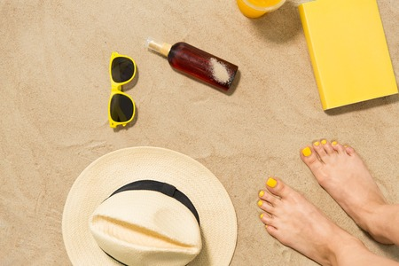 vacation and summer holidays concept - female feet, sunglasses, straw hat, sunscreen and book on beach sand