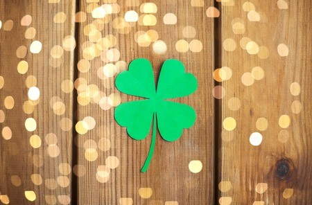 fortune, luck and st patricks day concept - green paper shamrock on wooden background