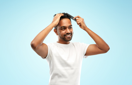 grooming, hairstyling and people concept - smiling young indian man brushing hair with comb over blue background