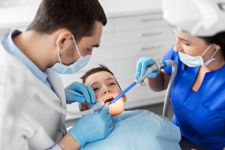 dentist treating kid teeth at dental clinic