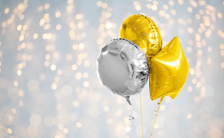 Tres globos de helio de oro y plata sobre blanco.