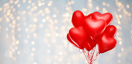 red heart shaped helium balloons on white Stockfoto
