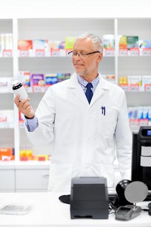 senior apothecary with drug at pharmacy