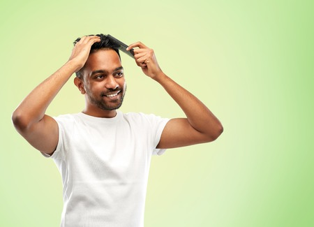 happy indian man brushing hair with comb