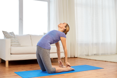 woman doing camel yoga pose at home