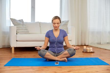 Mujer con música en smartphone meditando en casa