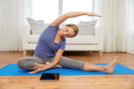 woman with tablet computer doing yoga at home