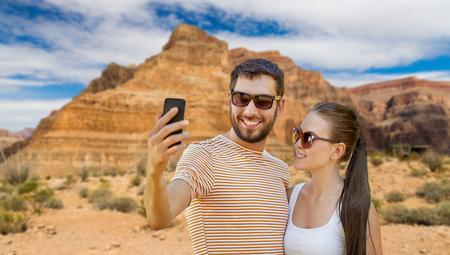 happy couple taking selfie by smartphone in summer