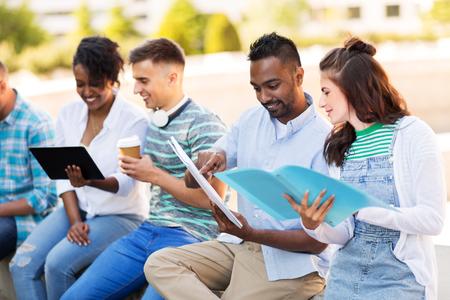 international students with notebooks outdoors