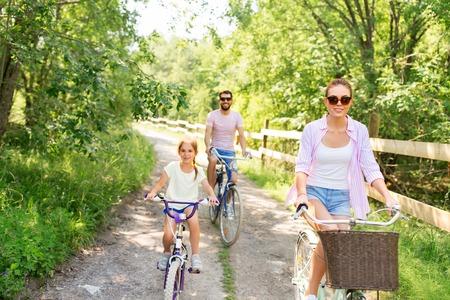 famille heureuse avec des vélos dans le parc d'été